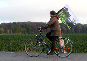"""A woman with a flag reading: """"Stop brown coal"""" rides a bike, with the ancient forest """"Hambacher Forst"""" in the background, in Kerpen-Buir"""
