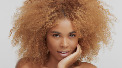 mixed race black blonde model with curly hair chin down watching to the camera
