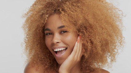 mixed race black blonde model with curly hair and laughing and put her face on hand