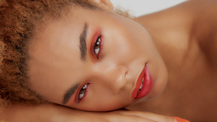closeup mixed race black woman with red makeup lying down on her own hand