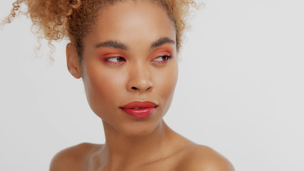 closeup portrait of mixed rase woman with red makeup in studio serious wathing aside