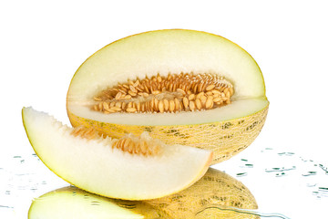 Sliced melon with seeds and piece of melon on white mirror background with reflection with water drops isolated close up