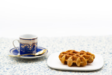 coffee and belgian waffle on flower pattern tablecloth