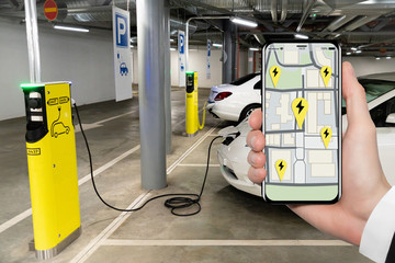 A hand with a phone on the background of a charging station for electric cars. On the screen is a map with the location of the charging stations.
