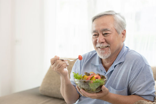 Lifestyle senior man feel happy enjoy eating diet food fresh salad on sofa