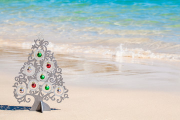 Wood christmas tree with decorations on sea coast with white sand and clear blue water on Phuket island, Thailand - concept of holidays and vacation in tropics