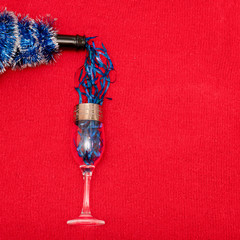 A bottle of champagne that pours tinsel into a glass. Background of red knitted fabric.