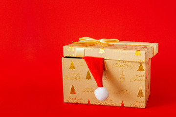 Christmas gift box with Santa Claus hat on red background