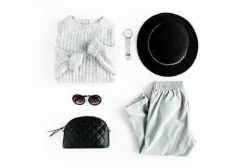 Wall Mural - Women fashion clothes and accessories. Feminine youth collage on white background top view. Flat lay female style look with warm sweater, pants, hat and sunglasses. Top view.