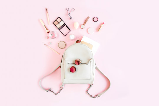 Women beige backpack and accessories on pink background top view. Flat lay female style look. Top view.