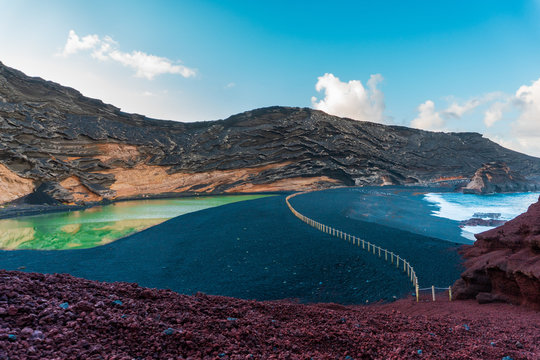 Volcanic landscape with a green lake and a black sand beach. Green Lagoon (El Lago Verde) at El Golfo, Lanzarote, Canary Islands, Spain.
