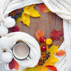 Autumn composition. Cup of coffee, colorful leaves and scarf on wooden background. Top View.