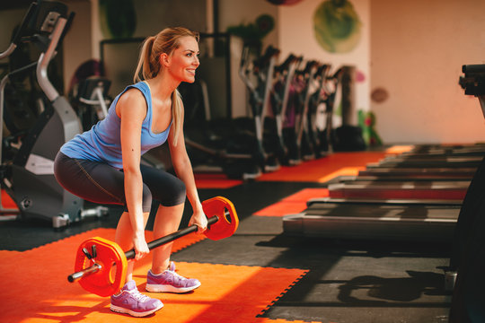 Young woman doing deadlift exercise in the gym