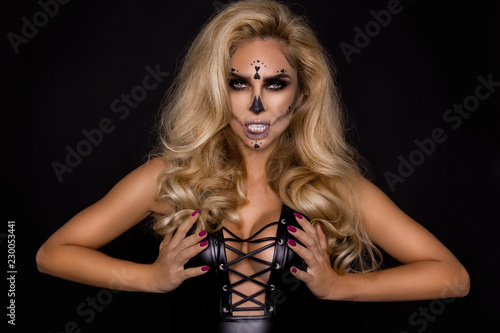 Sexy blonde woman in Halloween makeup and leather outfit on a black background in the studio. Skeleton, monster and witch.
