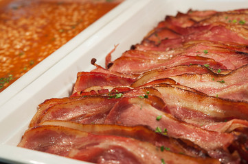 Closeup shot of trays of sliced grilled bacon and baked beans, healthy cooked breakfast options, adding protein and fiber to a diet. Horizontal shot with selective focus, concept for buffet-style meal