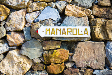 Arrow sign to the Manarola village on a stone wall.