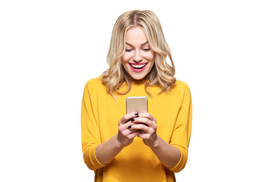 Excited young woman looking at her mobile phone smiling. Woman reading text message on her phone, isolated over white background.