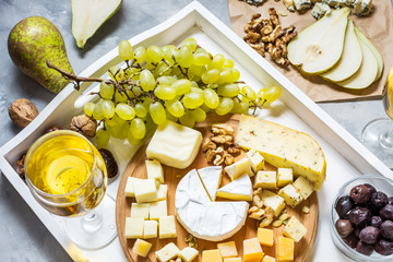 Different types of cheese on wooden board, olive, fruits, almond and wine glasses on white tray