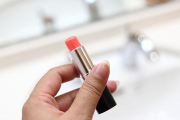 化粧をするためにリップスティックのボトルを持つ女性