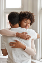Shot of diverse couple cuddle each other, express truthful feelings, enjoy togetherness, pleased to help one another in difficult situation. Old best friends embrace indoor, meet after long time