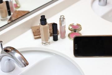 洗面でメイクをする リキッドファンデーション、リップスティック、スマートフォン