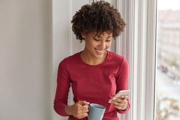 Happy pretty black girl happy to develop her own blog, rejoices having many followers, reads comments, drinks hot beverage, dressed in red clothes, stands near window. Hipster dials phone number