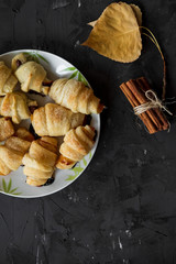 Small homemade croissants on a black background
