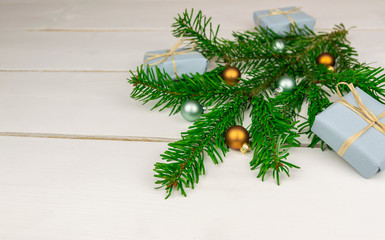 Christmas presents with a spruce twig and decorations on a white background.