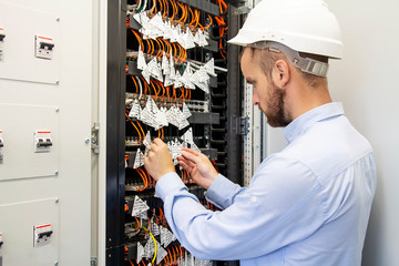 Technician engineer connects optical fibers into communication switch in data center