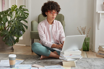 Black businesswoman keyboards on laptop computer, makes diploma paper, uses laptop which stands on pile of books, drinks takeaway coffee, sits crossed legs on floor, busy working. Studying concept