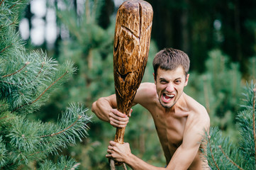Odd primitive naked man with huge wooden stick hunting in forest. Adult male have fun like crazy psyche with rude club in hands. Expressive excited boy face.  Wild masculine strength. Cruel warrior.