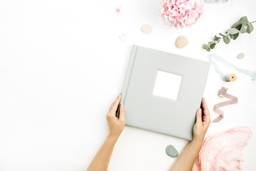 Woman hands holding wedding or family photo album. Hydrangea flower bouquet, eucalyptus branch, pastel pink blanket, monstera leaf decor on white background. Flat lay, top view still life concept.