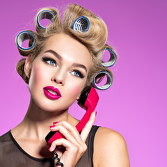 Young beautiful woman talking by a red vintage phone.