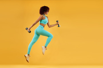 Strong athletic, woman sprinter or runner, running on yellow background with dumbbells wearing sportswear. Fitness and sport motivation.