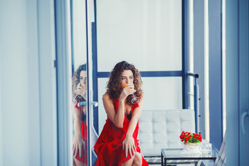 Young beautiful woman in red dress drinking juice indoor