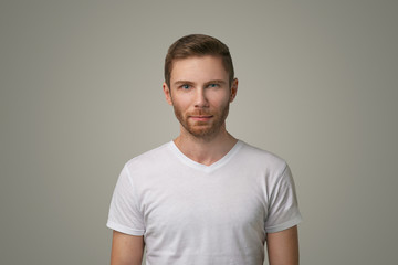Isolated shot of young handsome man with beard, moustache and fashionable hair, wearing casual white t-shirt, posing in Studio on white background. A man has a serious expression