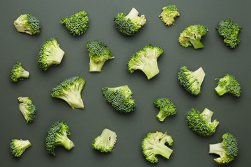 Broccoli pattern isolated on a dark green background. Various multiple parts of broccoli flower. Top view.