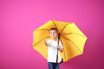 Little boy with yellow umbrella on color background