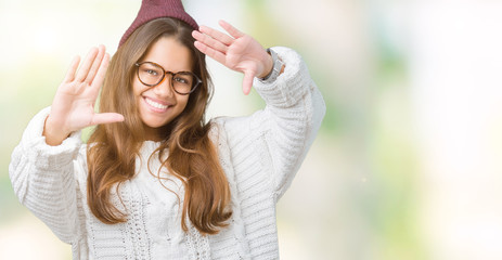 Young beautiful brunette hipster woman wearing glasses and winter hat over isolated background Smiling doing frame using hands palms and fingers, camera perspective