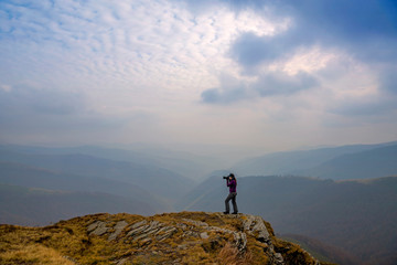 Photographer taking pictures of the mountains on a cloudy day. Beautiful autumn landscape in the mountains. Carpathian, Ukraine.
