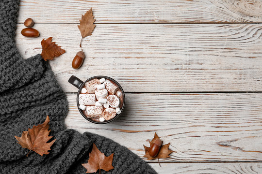 Flat lay composition with hot cozy drink and autumn leaves on wooden background. Space for text
