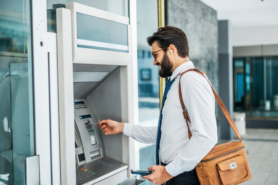 Businessman using card at an ATM