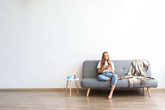 Young beautiful woman wearing white t-shirt on grey textile sofa at home. Attractive slim female in domestic situation, resting on couch in her lofty apartment. Background, copy space, close up.