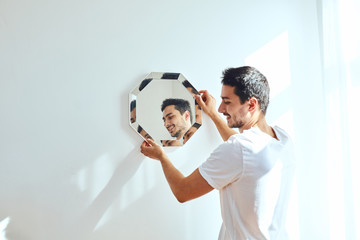 Studio portrait of young man standing near wall and hang mirror