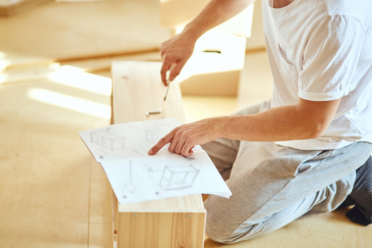 Concentrated young man reading instructions to assemble furniture at home