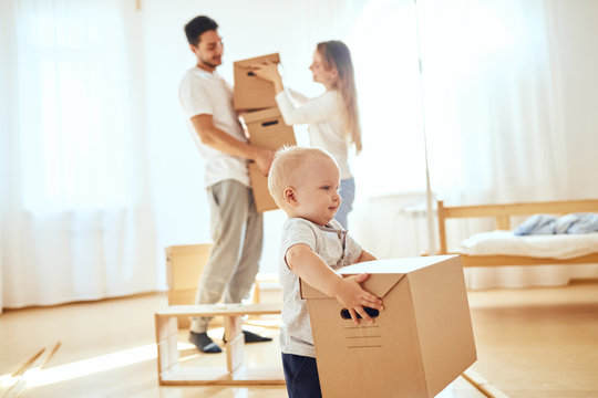 Happy little boy carrying moving box, parents on blurred background. Moving concept