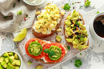 Vegetarian Healthy bread toasts with cottage cheese, heirloom tomatoes, scrambled eggs and avocado