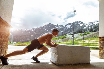 Handsome european crossfit male athlete with naked torso pushing stone block, outdoor crossfit work out over mountain nature background.