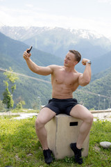 Handsome bodybuilder with perfect muscular body and blonde hair holding smart phone and taking a selfie outdoors over beautiful mountains with green flora on background.