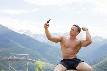 Young athlete half naked caucasian blonde man making photos of his well-trained strong body over beautiful mountains landscape to promote and advertise sports and healthy lifestyle.